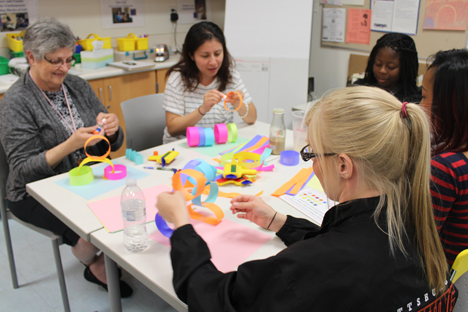 Student instructors learning methods of crafting with colored paper.