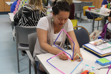 Student instructor uses colorful straws to build with.