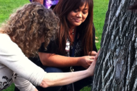 Student instructors make observations of sense and wonder by touching a tree.